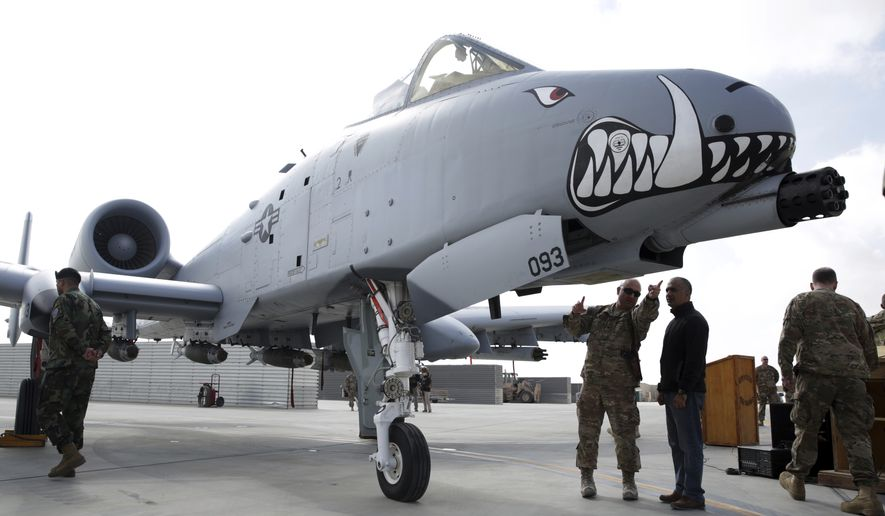 U.S. military forces stand beside an A-10C Thunderbolt II ground attack aircraft during an air show at Kandahar Airfield, Afghanistan, Tuesday, Jan. 23, 2018. (AP Photo/Massoud Hossaini)