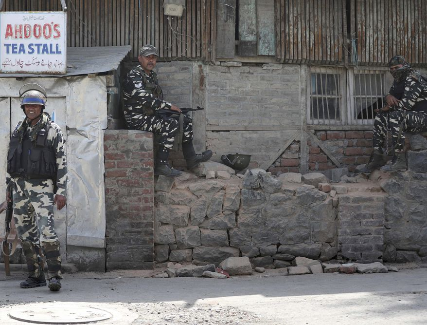 Indian paramilitary soldiers keep guard outside the main telephone exchange building in Srinagar, Indian controlled Kashmir, Thursday, Sept. 5, 2019. The Indian government stripped the Indian-administered portion of Kashmir of its limited autonomy on Aug. 5. Authorities imposed a sweeping military curfew that's still in place, and cut off residents from all communication and the internet. Mobile phone services have yet to be restored. (AP Photo/Mukhtar Khan)