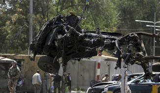 Resolute Support (RS) forces remove a destroyed vehicle after a car bomb explosion in Kabul, Afghanistan, Thursday, Sept. 5, 2019. The Afghan government says at least 10 civilians are dead and another 42 wounded after a Taliban suicide car bombing rocked the Afghan capital near a neighborhood housing the U.S. Embassy and the NATO Resolute Support mission. (AP Photo/Rahmat Gul)