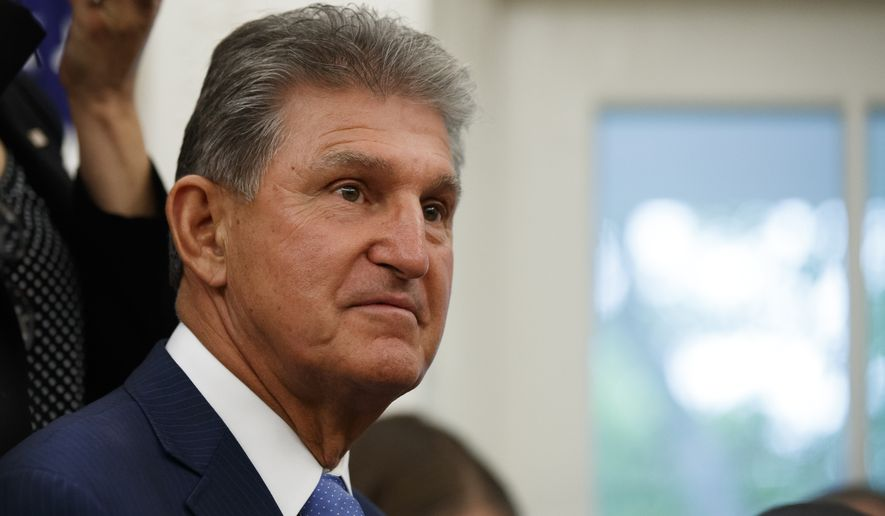 Sen. Joe Manchin, D-W.Va., stands as President Donald Trump speaks while presenting the Presidential Medal of Freedom to former NBA basketball player and general manager Jerry West, in the Oval Office of the White House, Thursday, Sept. 5, 2019, in Washington. (AP Photo/Alex Brandon)