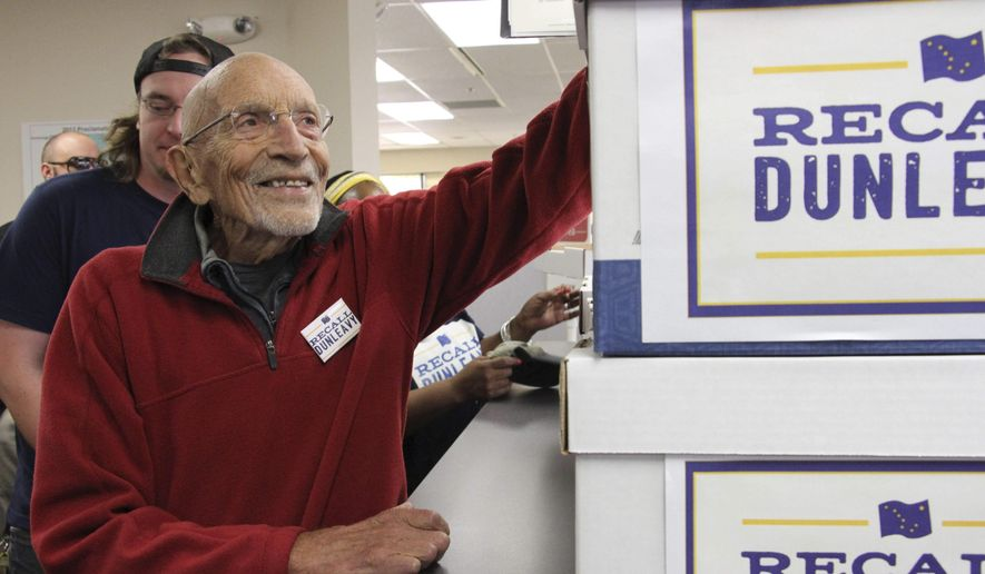 Vic Fischer, the last living person to help write the Alaska State Constitution, is shown smiling while looking at boxes of signatures to recall Alaska Gov. Mike Dunleavy that were delivered to the Alaska Division of Elections office in Anchorage, Alaska, on Thursday, Sept. 5, 2019. Fischer is one of the recall organizers, who say they submitted 49,0006 signatures in in an attempt to force the recall election of the first-term governor. (AP Photo/Mark Thiessen)