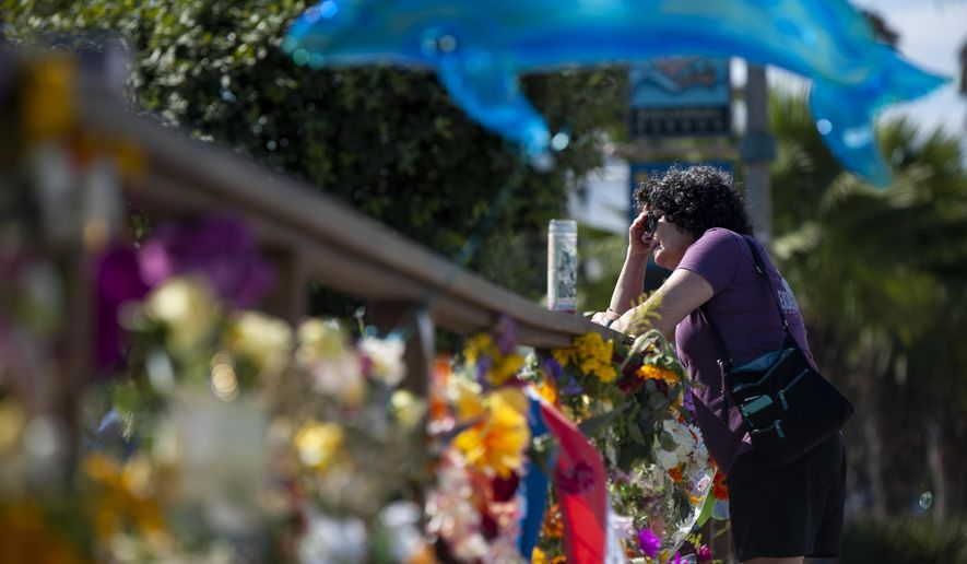 A woman gets emotional after placing flowers at a memorial for the victims of the Conception in the Santa Barbara Harbor on Wednesday, Sept. 4, 2019 in Santa Barbara, Calif. A fire raged through the boat carrying recreational scuba divers anchored near an island off the Southern California Coast on Monday, leaving multiple people dead. (AP Photo/Christian Monterrosa)