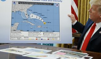President Donald Trump holds a chart as he talks with reporters after receiving a briefing on Hurricane Dorian in the Oval Office of the White House, Wednesday, Sept. 4, 2019, in Washington. (AP Photo/Evan Vucci)