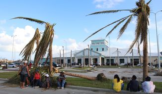 People sit under broken palm trees outside the Leonard M. Thompson International Airport after the passing of Hurricane Dorian in Marsh Harbour, Abaco Islands, Bahamas, Thursday, Sept. 5, 2019. Thousands of desperate people are seeking help in Dorian's aftermath. (AP Photo/Gonzalo Gaudenzi)