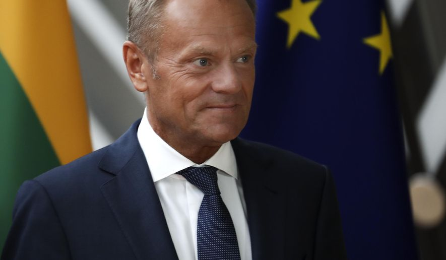 European Council President Donald Tusk walks by the EU flag prior to a meeting with Lithuania's Gitanas Nauseda at the European Council headquarters in Brussels, Thursday, Sept. 5, 2019. The British parliament moved to take a no-deal Brexit off the table, raising questions about whether the deadline for Britain to leave should be pushed back beyond October 31. (AP Photo/Francisco Seco)