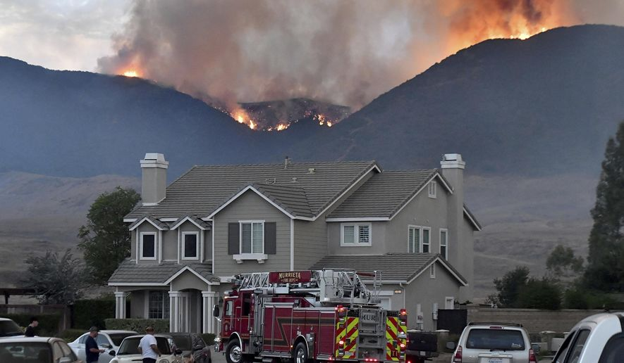 In this Wednesday, Sept 4, 2019 photo, Murrieta Fire Department engine pulls down Sherry Lane as the Tenaja Fire burns in and above Cole Canyon in Murrieta, Calif. (Will Lester/The Orange County Register via AP)