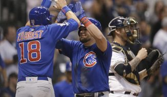 Chicago Cubs' Kyle Schwarber, middle, gets a high-five from Ben Zobrist after Schwarber's grand slam against the Milwaukee Brewers during the sixth inning of a baseball game Thursday, Sept. 5, 2019, in Milwaukee. (AP Photo/Jeffrey Phelps)