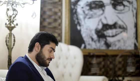 FILE - In this Sept. 30, 2018 photo, Abdullah Morsi, the youngest son of Egypt's jailed former Islamist President Mohamed Morsi, sits in front of a framed image of his father that was printed on a flag during the 2013 Rabaah al-Adawiya sit-in, at his home in Cairo, Egypt. Physicians said 25-year-old Abdullah Morsi died of a heart attack shortly after arriving in hospital Wednesday, Sept 4, 2019. His father collapsed and died in a Cairo court in June. (AP Photo/Brian Rohan, File)