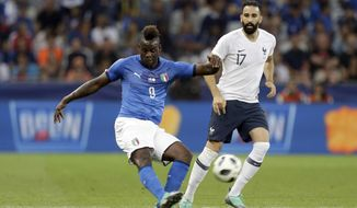 FILE -  In this Friday, June 1, 2018 file photo, Italy's Mario Balotelli, left, kicks the ball while France's Edil Rami looks on during a friendly soccer match between France and Italy at the Allianz Riviera stadium in Nice, southern France. Italy coach Roberto Mancini has set the bar high for Mario Balotelli's chances of returning to the national team. Balotelli recently returned to Serie A with Brescia, his hometown club, but his season hasn't started yet as he serves a four-match ban following a straight red card in his final game for Marseille against Montpellier in May. (AP Photo/Claude Paris, File)