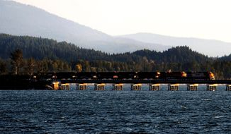 FILE - In this Sept. 16, 2014, file photo, a train crosses Lake Pend Oreille as it leaves Sandpoint, Idaho. Federal officials say BNSF Railway's plan to build two bridges as part of a second railroad line in northern Idaho meets environmental requirements. The U.S. Coast Guard on Thursday, Sept. 5, 2019, issued a final environmental assessment for the bridges across Lake Pend Oreille and Sand Creek at Sandpoint, finding no significant impact. The Coast Guard is involved because the structures are over navigable waters. Idaho officials have already approved the bridges. (Kathy Plonka/The Spokesman-Review via AP, File)