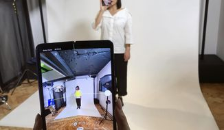 FILE - In this April 16, 2019, file photo, a model holds a Samsung Galaxy Fold smart phone to her face, during a media preview event in London. Samsung says it will start selling its highly anticipated folding phone on Friday Sept. 6, 2019, after its original launch date was delayed by months because of embarrassing problems with the screen. (AP Photo/Kelvin Chan, File)