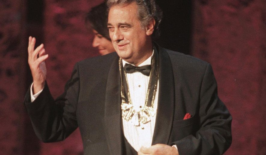 """FILE - In this Tuesday, Sept. 14, 1999 file photo, Placido Domingo acknowledges the audience after receiving the 1999 Hispanic Heritage Award at the John F. Kennedy Center for the Performing Arts in Washington. An evening before a performance of """"Le Cid,"""" part of the Washington Opera's 1999-2000 season, opera singer Angela Turner Wilson said she and Domingo were having their makeup done together when he rose from his chair, stood behind her and put his hands on her shoulders. As she looked at him in the mirror, he suddenly slipped his hands under her bra straps, she said, then reached down into her robe and grabbed her bare breast. """"It hurt,"""" she told The Associated Press. """"It was not gentle. He groped me hard."""" She said Domingo then turned and walked away, leaving her stunned and humiliated. (AP Photo/Leslie Kossoff)"""
