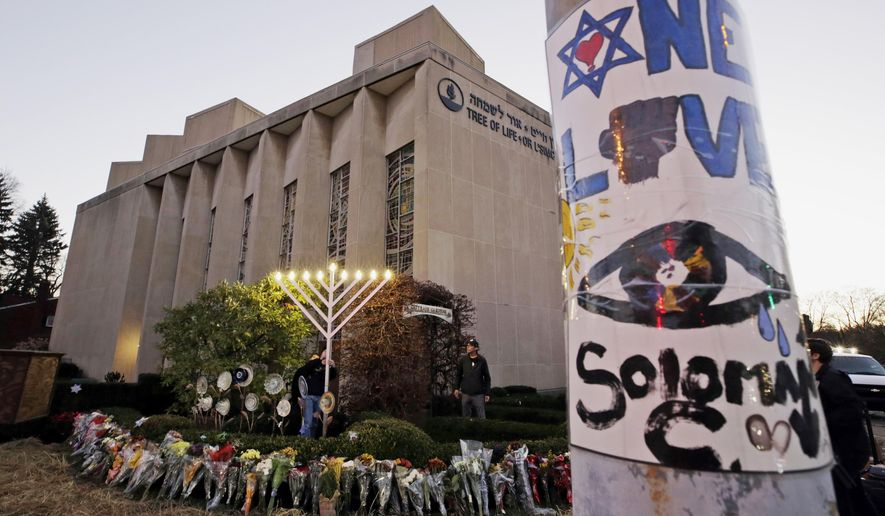 FILE - This Dec. 2, 2018, file photo shows a menorah at a memorial outside the Tree of Life Synagogue, where Robert Bowers killed worshippers in an Oct. 27 shooting, as people prepare for a celebration service at sundown on the first night of Hanukkah in the Squirrel Hill neighborhood of Pittsburgh.   Federal prosecutors are recommending a 10-month prison sentence and supervised release for Jeffrey Clark Jr., whose relatives reported concerns about his behavior and far-right extremist rhetoric after last year's Pittsburgh synagogue massacre.  He is scheduled to be sentenced Sept. 13, 2019 in Washington. (AP Photo/Gene J. Puskar, File)