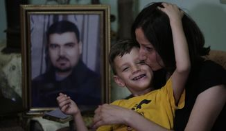 In this July 26, 2019 photo, schoolteacher Suzan Suleiman hugs and kisses her son Youssef, 6, during an interview in Homs, Syria. Six months after he was snatched from a road in central Syria, Iyad Suleiman, a father of three, was allowed by his kidnappers to make a Skype video call home. His children were startled at how he looked skinny and exhausted, with a long beard. That two-minute call in September 2013 was the last Suleiman's family saw of him. (AP Photo/Hassan Ammar)