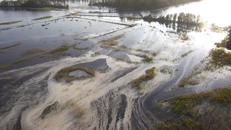 FILE - In this file image made from Sept. 21, 2018 drone video provided by the N.C. Department of Environmental Quality, light gray material flows out of a flooded coal ash dump toward the Cape Fear River at Duke Energy's L.V. Sutton Power Station near Wilmington, N.C. Duke Energy said Wednesday, Sept. 4, 2019, that it had completed extensive repairs to the dam that breached during Florence at the L.V. Sutton Power Station. (N.C. Department of Environmental Quality via AP, File)
