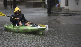 Johnny Crawford navigates his kayak down a flooded street, Thursday, Sept. 5, 2019, in Charleston, S.C., following Hurricane Dorian. The downtown neighborhood is prone to floodwaters, even without a tropical weather event. (AP Photo/Meg Kinnard)