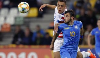 FILE - In this May 24, 2019, file photo, Ukraine's Serhii Buletsa, front, duels for the ball with United States' Sergino Dest during a Group D U20 World Cup soccer match in Bielsko Biala, Poland. Dest, an 18-year-old Ajax outside back eligible for the United States and the Netherlands, could make his U.S. debut in Friday's exhibition against Mexico but also has been in contact with the Dutch soccer federation. (AP Photo/Sergei Grits, File)