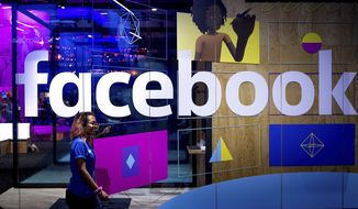 In this Tuesday, April 18, 2017, file photo, a conference worker passes a demo booth at Facebook's annual F8 developer conference, in San Jose, Calif.  New York Attorney General Letitia James says a bipartisan coalition of state attorneys general is investigating Facebook for alleged antitrust issues. James said Friday, Sept. 6, 2019 the probe will look into whether Facebook's actions endangered consumer data, reduced the quality of consumers' choices or increased the price of advertising.   (AP Photo/Noah Berger, File)