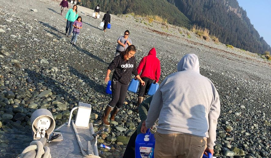 This Aug. 29, 2019, photo provided by Katrina Berestoff shows residents of Nanwalek, Alaska, filling up water jugs in the nearby Kenai Peninsula community of Port Graham. Alaska's hot, dry summer has led to extreme measures for extreme drought conditions for the Native communities of Nanwalek and Seldovia, prompting regional officials to declare a disaster declaration. (Katrina Berestoff via AP)