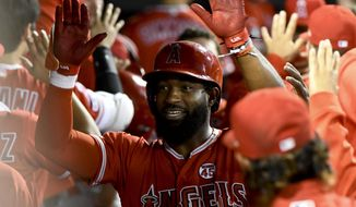 Los Angeles Angels' Brian Goodwin celebrates in the dugout after hitting a two-run home run off Chicago White Sox's Aaron Bummer during the eighth inning of a baseball game Friday, Sept. 6, 2019, in Chicago. (AP Photo/Matt Marton)