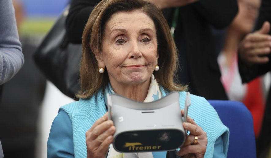 U.S. House Speaker Nancy Pelosi holds a virtual reality mask as she visits the French Research Institute for the Exploitation of the Sea (IFREMER), in Brest, western France, Friday, Sept. 6, 2019. The leaders of parliament of the Group of Seven leading democracies are meeting in France to discussing protecting the world's oceans and other international cooperation. The G-7 includes the United States, France, Britain, Germany, Japan, Canada and Italy. (AP Photo/David Vincent, Pool)