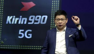Richard Yu, CEO of the Huawei consumer business group, holds a 'Kirin 990 5G' processor during a keynote at the IFA 2019 tech fair in Berlin, Germany, Friday, Sept. 6, 2019. The IFA takes place in Berlin from Sept. 6 until Sept. 11, 2019. (AP Photo/Michael Sohn)