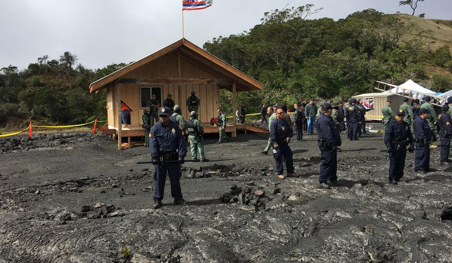 Crews and police gather at a lava field on Hawaii's Mauna Kea on the big island on Friday, Sept. 6, 2019 while a small wooden house is demolished. Opponents of a giant telescope built the unpermitted structure near their protest camp. (Dan Dennison/Department of Land and Natural Resources via AP)