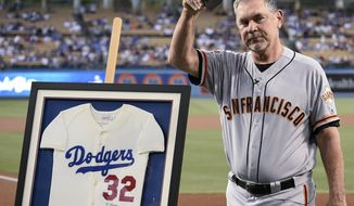 San Francisco Giants manager Bruce Bochy acknowledges the crowd after receiving a signed Sandy Koufax jersey to commemorate his last series at Dodger Stadium as Giants manager, prior to the team's baseball game against the Los Angeles Dodgers in Los Angeles, Friday, Sept. 6, 2019. (AP Photo/Kelvin Kuo)