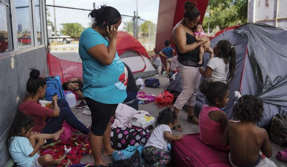 In this Aug. 30, 2019, photo, a group of Mexican asylum seekers wait near the Gateway International Bridge in Matamoros, Mexico. Pregnant women face special hazards in Mexico because places where migrants wait to enter the U.S. often don't have access to regular meals, clean water, and medical care. (AP Photo/Veronica G. Cardenas) **FILE**
