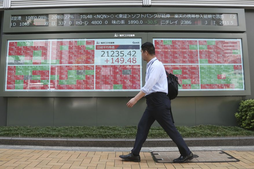 A man walks by an electronic stock board of a securities firm in Tokyo, Friday, Sept. 6, 2019. Asian shares rose Friday as investors cheered plans for more trade negotiations between Washington and Beijing and drew encouragement from positive data about the U.S. economy. (AP Photo/Koji Sasahara)