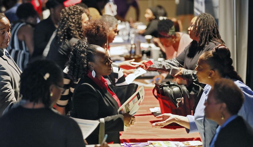 In this Aug. 14, 2019, file photo company representatives from Verizon, Goodwill, Kaiser Permanente and UPS, right, talk with potential applicants during a job and resource fair in Atlanta. (Bob Andres/Atlanta Journal-Constitution via AP, File)