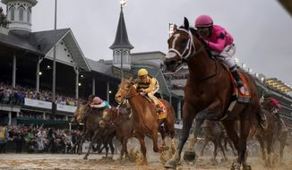 FILE - In this May 4, 2019, file photo, jockey Flavien Prat, aboard Country House, center, looks on as jockey Luis Saez, right, aboard Maximum Security, crosses the finish line during the 145th running of the Kentucky Derby horse race at Churchill Downs in Louisville, Ky. Country House was declared the winner after Maximum Security was disqualified following a review by race stewards. The home of the Kentucky Derby wants to start offering live racing in the winter. Churchill Downs says it will seek approval from Kentucky horse racing regulators to allow the Louisville track to host live racing in the winter of 2020. (AP Photo/Matt Slocum, File)