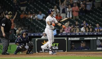Houston Astros' Michael Brantley, right, watches his game-winning two-run home run along with Seattle Mariners catcher Austin Nola, center, during the 13th inning of a baseball game Thursday, Sept. 5, 2019, in Houston. The Astros won 11-9. (AP Photo/David J. Phillip)