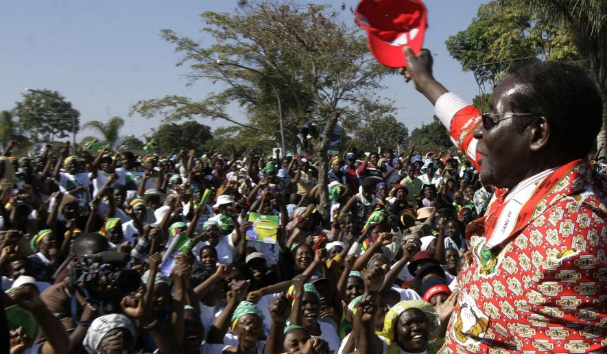 FILE - In this Thursday, June 26, 2008 file photo, Zimbabwe's President Robert Mugabe, right, greets the crowd at his final rally in Chitungwiza, Zimbabwe. Mugabe, the longtime leader of Zimbabwe who was forced to resign in 2017 after a military takeover, has died at 95. (AP Photo/Tsvangirayi Mukwazhi, file)