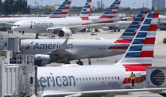 FILE - In this April 24, 2019, photo, American Airlines aircraft are shown parked at their gates at Miami International Airport in Miami. An American Airlines mechanic is accused of sabotaging a flight from Miami International Airport to Nassau in the Bahamas, over stalled union contract negotiations. Citing a criminal complaint affidavit filed in federal court, The Miami Herald reports Abdul-Majeed Marouf Ahmed Alani was arrested Thursday, Sept. 5, 2019, on the sabotage charge and is accused of disabling the flight's navigation system. (AP Photo/Wilfredo Lee, File)