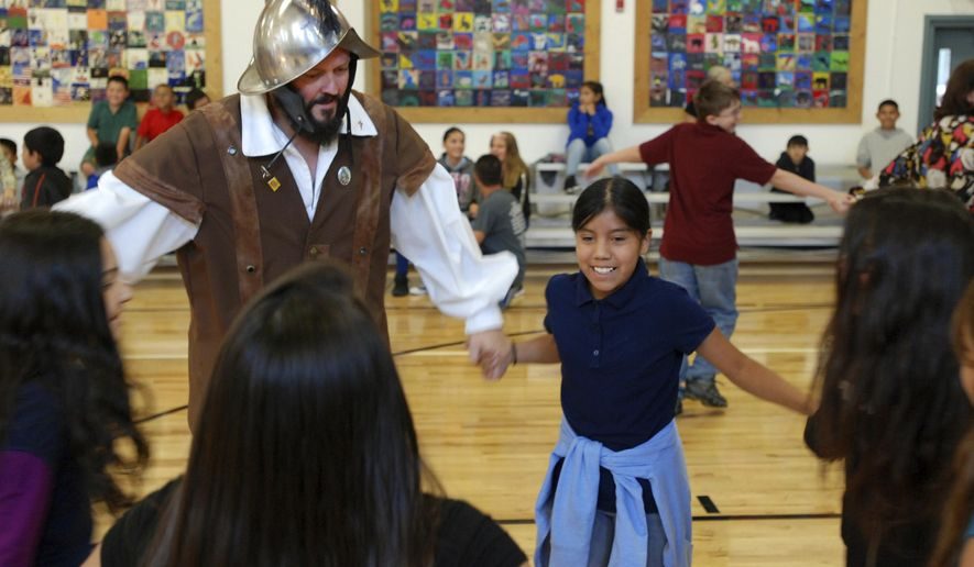 FILE - In this Aug. 30, 2017, file photo, Edwin Quintana, left, dances with fifth grader Kaylee Pacheco and other students at Tesuque Elementary school in Tesuque, N.M. Annual school visits by Spanish conquistador re-enactors in Santa Fe, N.M., the oldest capital city in North America, are being limited under new rules following criticism from Native American activists. (AP Photo/Morgan Lee, File)