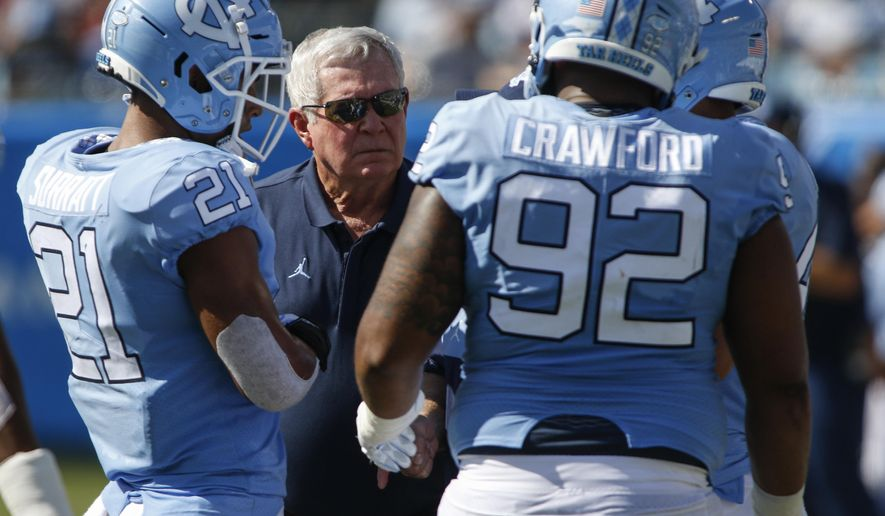 North Carolina head coach Mack Brown talks to linebacker Chazz Surratt (21) and defensive lineman Aaron Crawford (92) as they play South Carolina in the first half of an NCAA college football game  in Charlotte, N.C., Saturday, Aug. 31, 2019. (AP Photo/Nell Redmond)