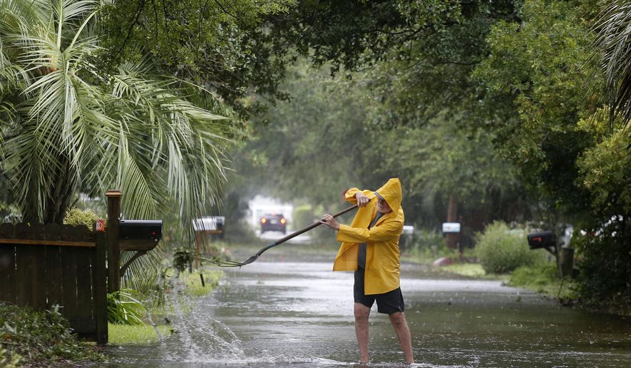 An Isle of Palms resident clears the drain on Hartnett Blvd. during Hurricane Dorian at the Isle of Palms, S.C., Thursday, Sept. 5, 2019, in Charleston, S.C. (AP Photo/Mic Smith)