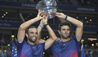 Juan Sebastian Cabal, left, and Robert Farah, both of Colombia, hold up the championship trophy after defeating Marcel Granollers, of Spain, and Horacio Zeballos during the men's doubles final of the U.S. Open tennis championships Friday, Sept. 6, 2019, in New York. (AP Photo/Sarah Stier)