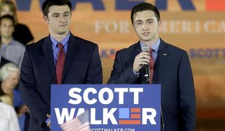 FILE - In this July 13, 2015, file photo, Wisconsin Gov. Scott Walker's son Alex, left, listens to his brother Matt, speak to supporters before their father announces he is running for the 2016 Republican presidential nomination in Waukesha, Wis. The former governor tells WISN-TV in an interview recorded Friday that his son Matt is interested in the seat being vacated by retiring Republican U.S. Rep. Jim Sensenbrenner. (AP Photo/Morry Gash, File)