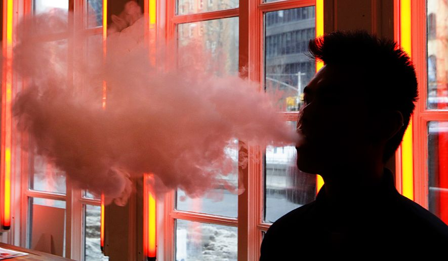 """A patron exhales vapor from an e-cigarette at a store in New York. Commenting that """"people should not be using vaping products, period,"""" (AP Photo/Frank Franklin II, File)"""