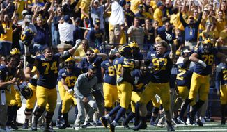 Michigan offensive lineman Ben Bredeson (74) and defensive lineman Aidan Hutchinson (97) celebrate after beating Army 24-21 in double-overtime in an NCAA college football game in Ann Arbor, Mich., Saturday, Sept. 7, 2019. (AP Photo/Paul Sancya)
