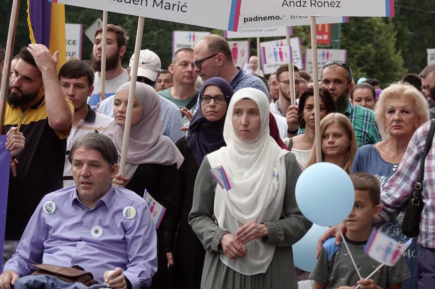 Holding banners and balloons, participants march in what they said was a gathering designed to promote traditional family values in Sarajevo, Bosnia, Saturday, Sept. 7, 2019. Several hundred people have marched in Bosnia's capital Sarajevo to express their disapproval of the Balkan country's first ever LGBT pride parade scheduled for Sunday. (AP Photo/Eldar Emric)