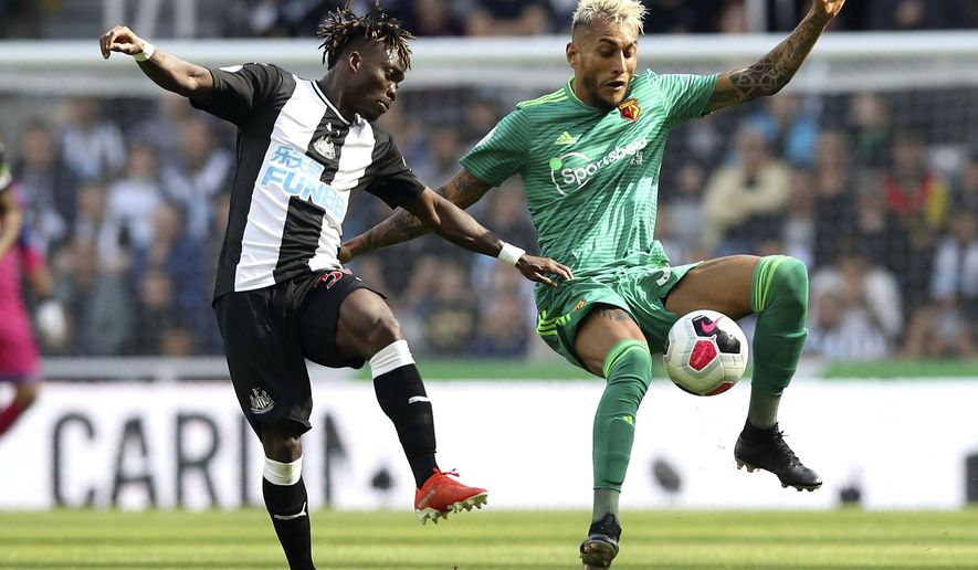 Newcastle United's Christian Atsu, left, and Watford's Roberto Pereyra battle for the ball during the English Premier League soccer match at St James' Park, London, Saturday Aug. 31, 2019. (Owen Humphreys/PA via AP)