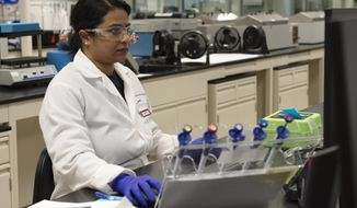 CORRECTS SPELLING TO MAMTA MANDAL, NOT MANTA MANDALN - In this Aug. 19, 2019 photo, Mamta Mandal reviews a procedure at Celerion in Lincoln, Neb. In 1969, the scientific company in Lincoln that was then called Harris Labs did its first clinical drug trial. (Emily Haney/Lincoln Journal Star via AP)