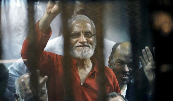 FILE - In this file photo dated Saturday, May 16, 2015, Muslim Brotherhood spiritual leader, Mohammed Badie waves from a defendants cage in a makeshift courtroom at the national police academy, in eastern Cairo, Egypt.  An Egyptian court on Saturday, Sept. 7, 2019,  sentenced 11 people to life in prison, including Mohammed Badie, after a retrial on charges related to mass prison breaks at the height of the 2011 popular uprising.  The retrial was related to a case rooted in the escape of 20,000 inmates from Egyptian prisons in Jan. 2011, early in the 18-day uprising that toppled longtime autocratic President Hosni Mubarak, who had testified in the case in December last year. The verdict cannot be appealed.  (AP Photo/Ahmed Omar, FILE)