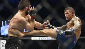 Russian UFC fighter Khabib Nurmagomedov, left, fights with UFC fighter Dustin Poirier, of Lafayette, La., during Lightweight title mixed martial arts bout at UFC 242, in Yas Mall in Abu Dhabi, United Arab Emirates, Saturday , Sept.7 2019. (AP Photo/ Mahmoud Khaled)