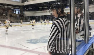 Linesman Kirsten Welsh watches at center ice as Pittsburgh Penguins and Boston Bruins players take the ice to prepare to play in the Sabres prospects hockey tournament, Friday, Sept. 6, 2019, in Buffalo, N.Y. Welsh is one four female officials selected to be the first women to work as on-ice officials at several prospect tournaments taking place across the country this weekend. The other three other women selected were Katie Guay, Kelly Cooke and Kendall Hanley. (AP Photo/John Wawrow)