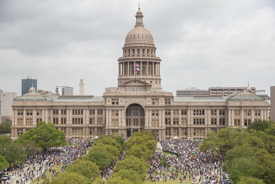 """In this March 24, 2018, file photo, thousands of people gather on the grounds of the Texas State Capitol during a """"March for Our Lives"""" rally in Austin, Texas.  The vast majority of mass shooters have acquired their firearms legally with nothing in their background that would have prohibited them from possessing a gun. But there have been examples of lapses in the background check system that allowed guns to end up in the wrong hands. Very few states also have a mechanism to seize firearms from someone who is not legally allowed to possess one.(Nick Wagner/Austin American-Statesman via AP, File)"""