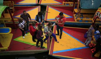 Passengers are helped to step between trajineras, colorful passenger boats typically rented by tourists, families, and groups of young people, as they board a boat in Xochimilco, Mexico City, Friday, Sept. 6, 2019. The usually festive Nativitas pier was subdued and largely empty Friday afternoon, with some boat operators and vendors estimating that business was down by 80% on the first weekend following the drowning death of a youth that was captured on cellphone video and seen widely in Mexico. Borough officials stood on the pier to inform visitors of new regulations that went into effect Friday limiting the consumption of alcohol, prohibiting the use of speakers and instructing visitors to remain seated.(AP Photo/Rebecca Blackwell)